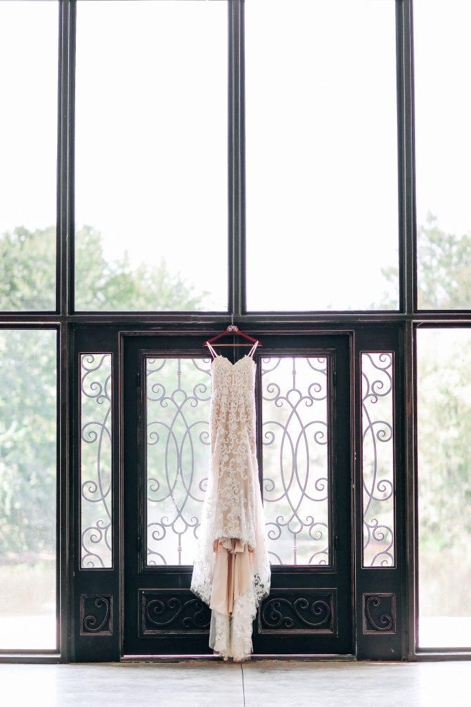 Wedding dress hangs in window.