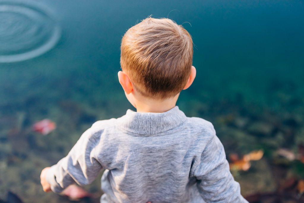 Little boy throwing rocks in a pond.