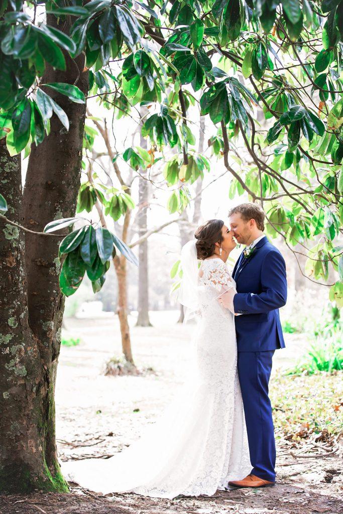 Couple kisses under magnolia tree.
