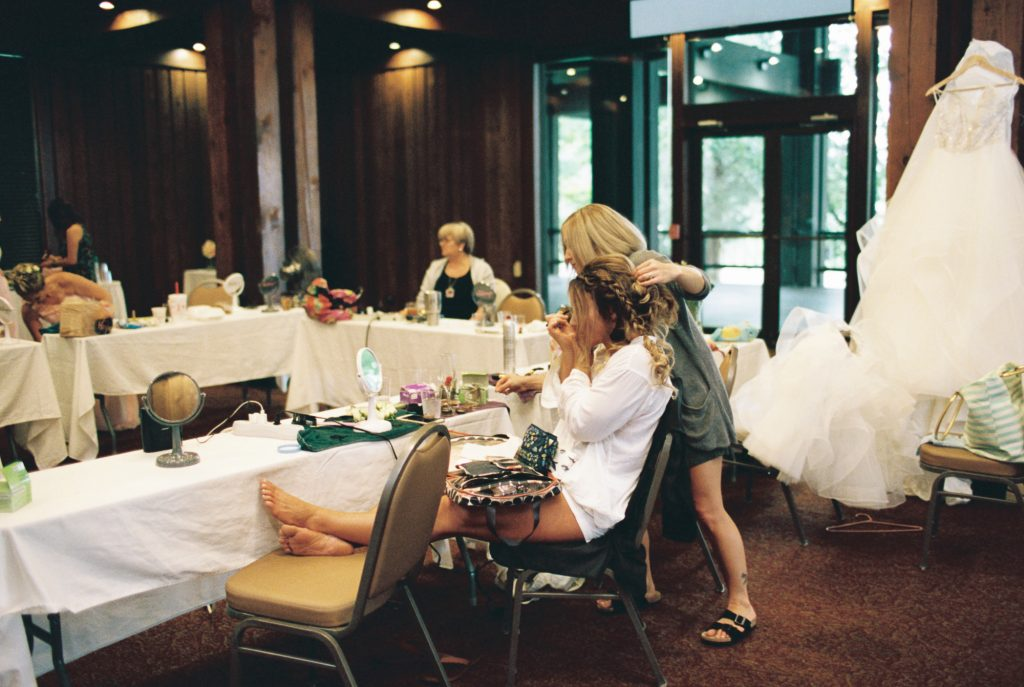 Bride in dressing room with hairstylist